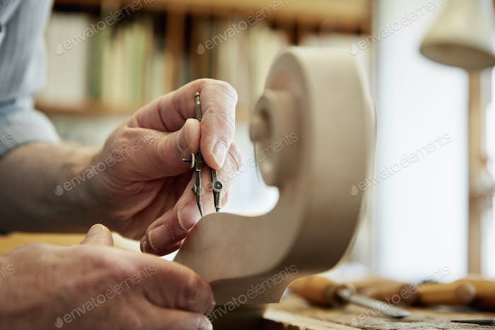 A violin maker working in his workshop, using hand tools to shape and chisel the curled scroll of
