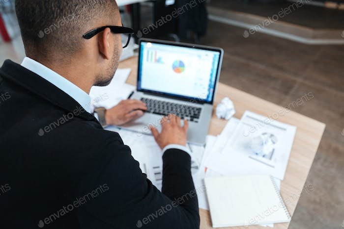 Back view of businessman typing on laptop