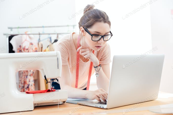 Serious woman seamstress using laptop in studio