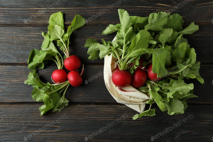 Bag with radish on wooden background, top view