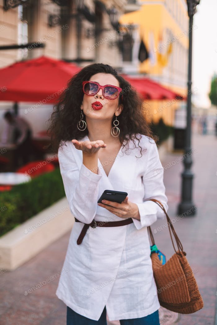 Beautiful stylish girl in sunglasses with cellphone in hand sending air kiss in camera on street