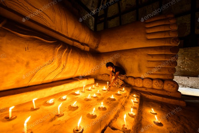 55202,Asian girl lighting prayer candles in Buddhist temple