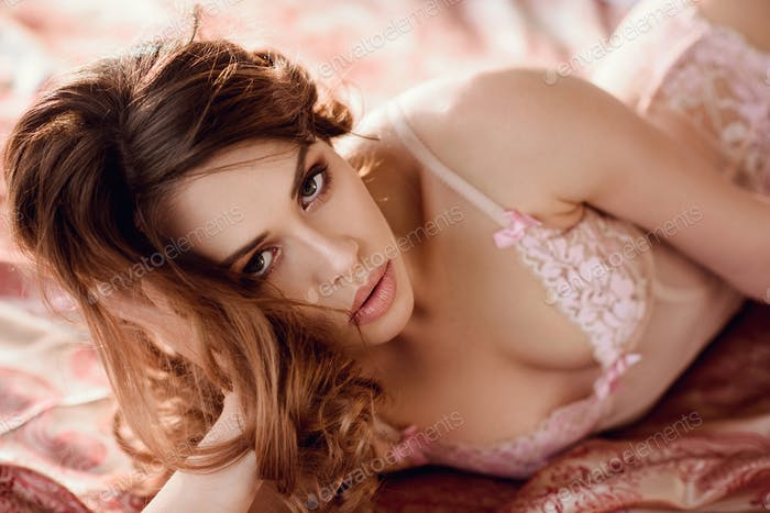 Fashionable female portrait of cute lady in pink bra indoors
