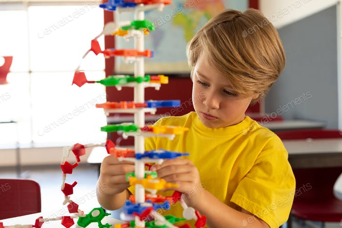 Front view of thoughtful Caucasian boy studying science model in classroom at elementary school