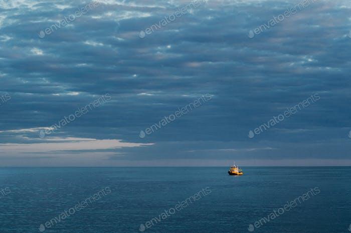 небольшой корабль в море против неба заката