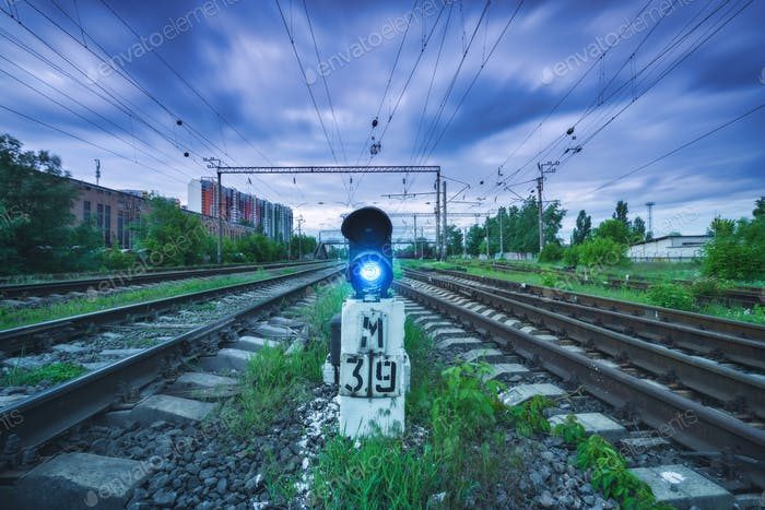 Railway station with traffic light and blurred sky with clouds