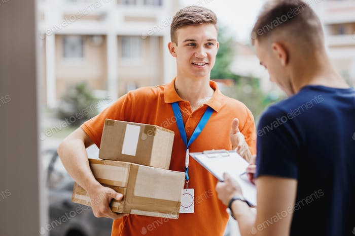A smiling person wearing an orange T-shirt and a name tag is delivering a parcel to a client, who is