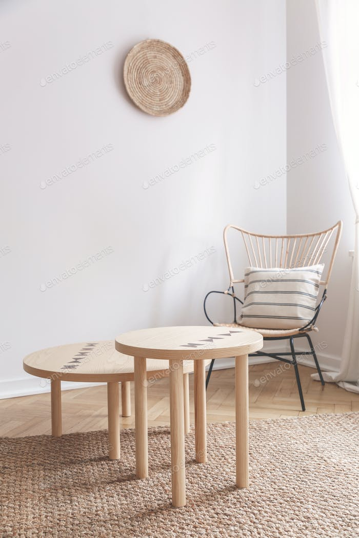 Two small coffee tables and wicker chair with pillow on it in na