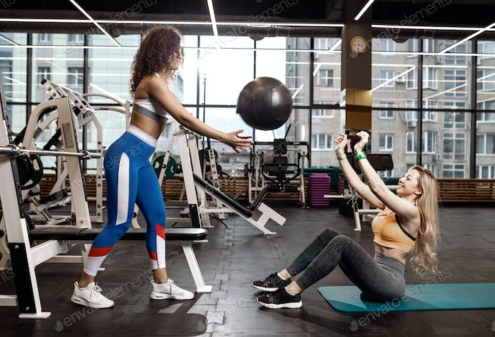 Two athletic girls dressed in a sportswear are doing exercises for the press on the mat for fitness