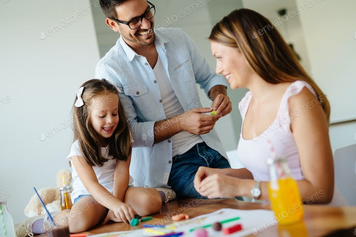 Little girl doing art work with her parents