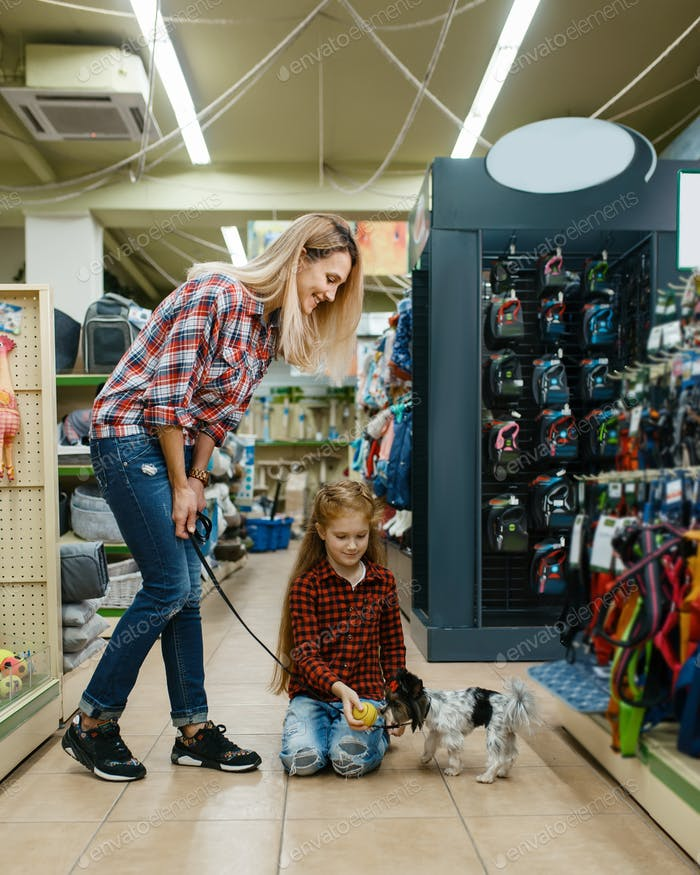 Mother with daughter choosing ball, pet store