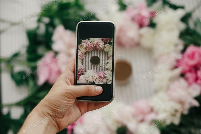 Hand holding phone and taking photo of peonies and coffee cup flat lay