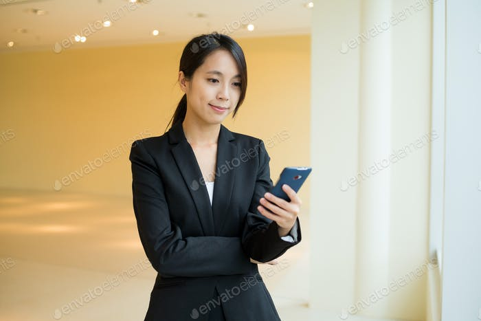 Asian Businesswoman check the text message on cellphone