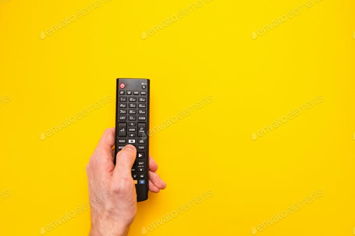 Television remote control in the hand isolated on yellow background