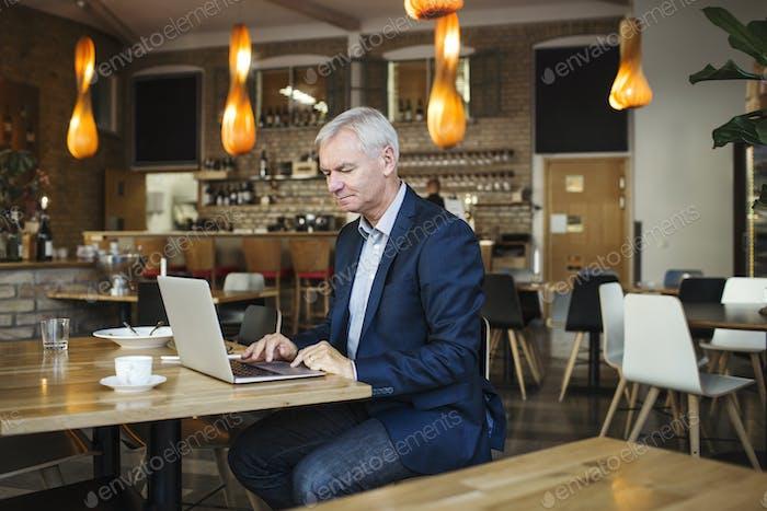 Konzentrierter Geschäftsmann mit Laptop am Tisch im Restaurant