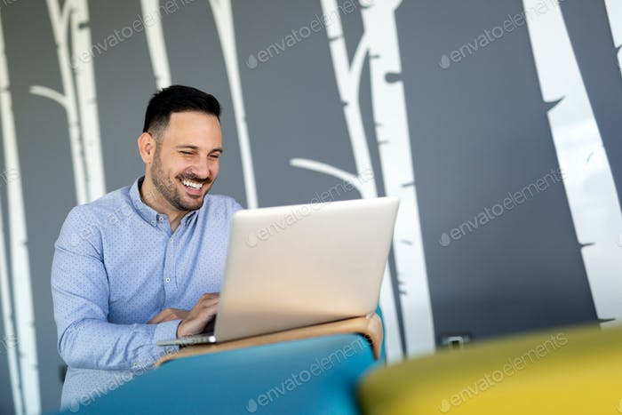 Smiling male blogger keyboarding article in electronic newspaper using laptop