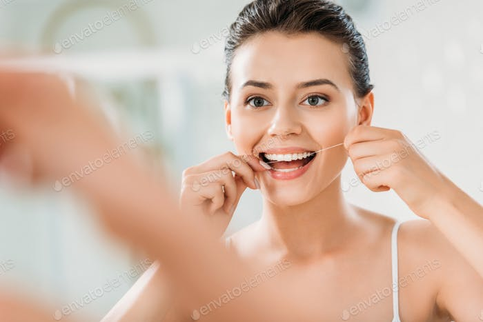 selective focus of beautiful smiling girl using dental floss in bathroom