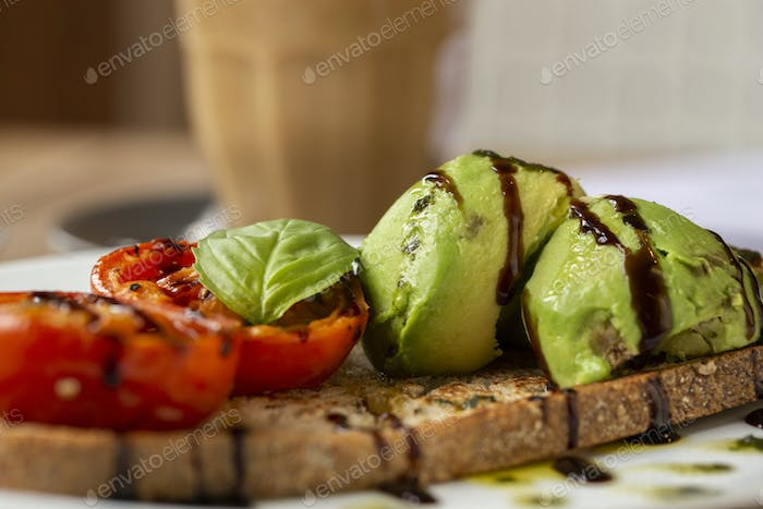Close up of tomato and avocado bruschetta with balsamic vinegar reduction in a cafe.