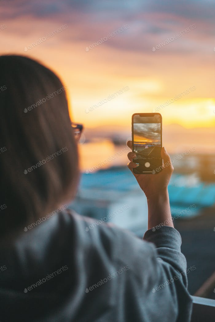 Woman taking photos of the sea from the balcony with a smartphone