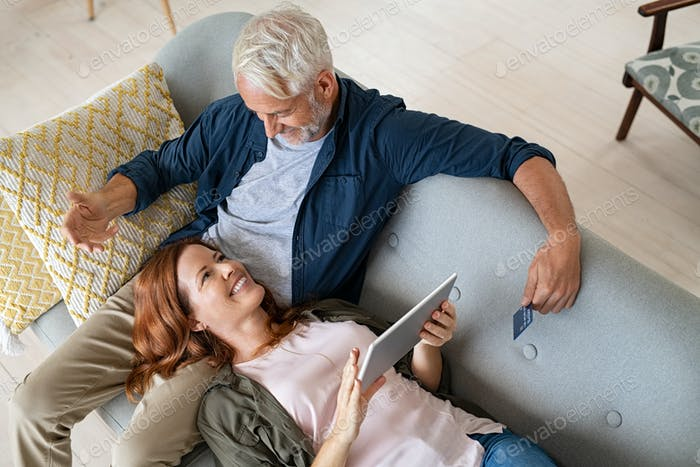 Happy couple using digital tablet with credit card