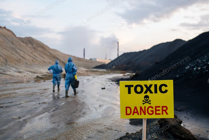 Announcement about toxic and dangerous area on background of ecologists
