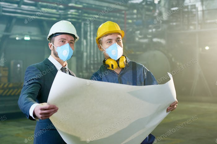 Engineers Holding Blueprints at Factory