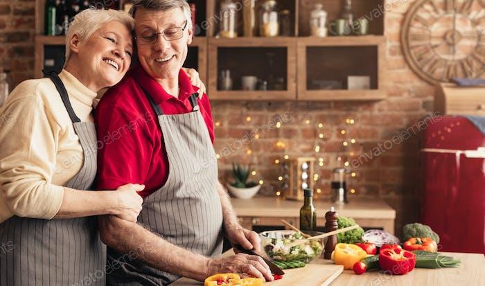 Grateful senior woman hugging her husband at kitchen