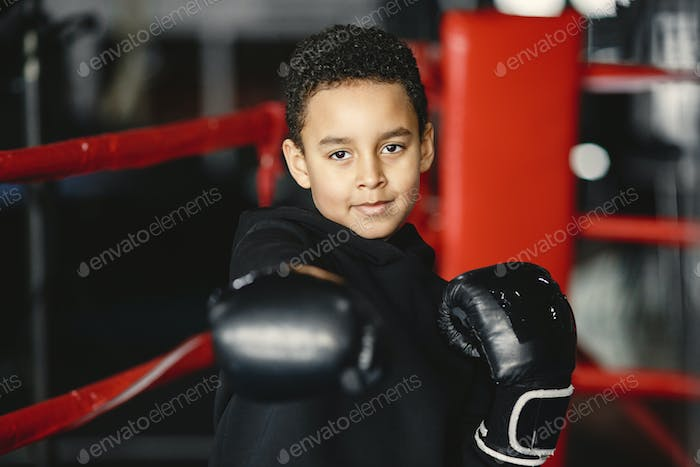 Little boy in boxing gloves on ring