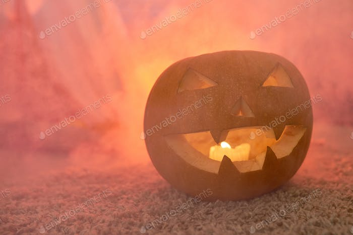 Scary carved pumpkin in smoke