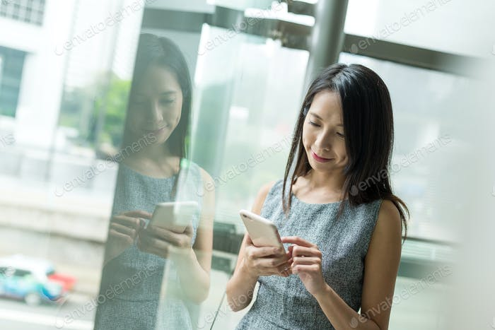 Businesswoman looking at cellphone inisde office