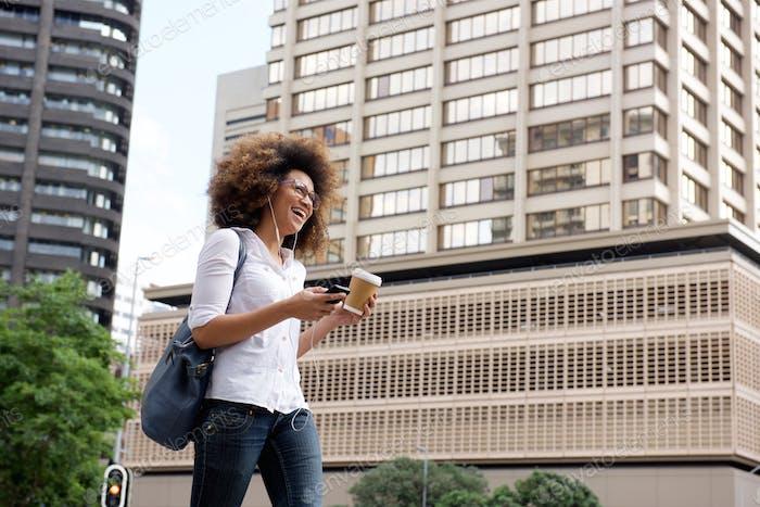 Junge Frau Musik hören und in der Stadt spazieren gehen