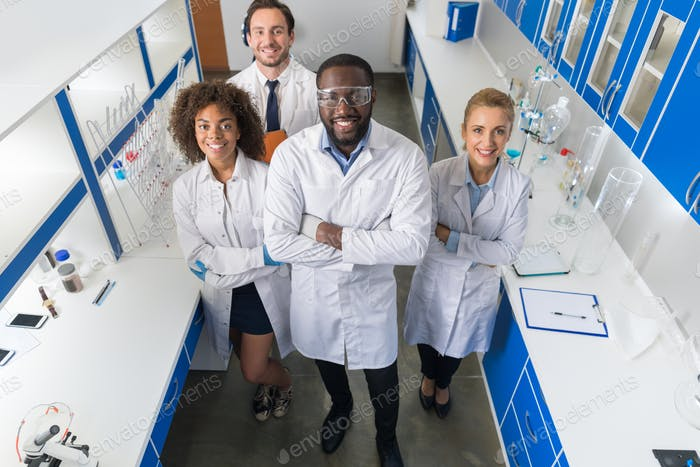 African American Scientist With Group Of Researchers In Modern Laboratory Happy Smiling, Mix Race