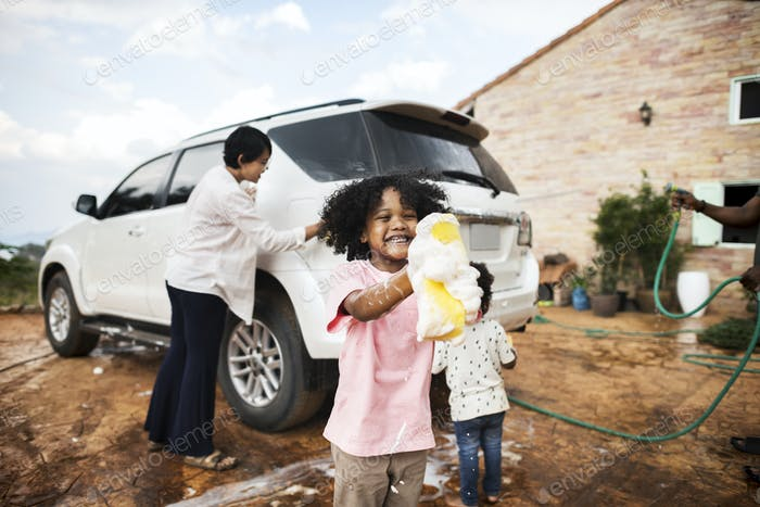 Family washing their white car