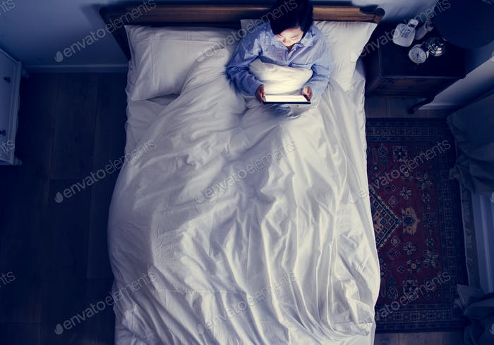 Woman in bed using a digital device in the dark