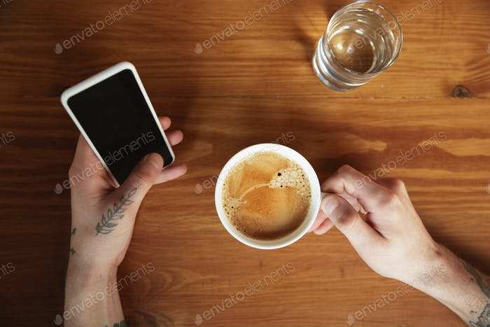 Top view of male hands using smartphone with blank screen, copyspace, education and business concept