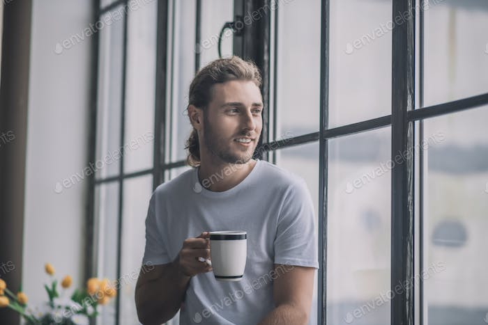 Inspired long-haired man having a cup of morning coffee.