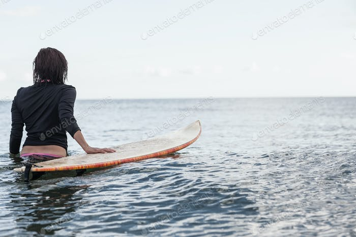 Rear view of a woman with surfboard in the water at beach