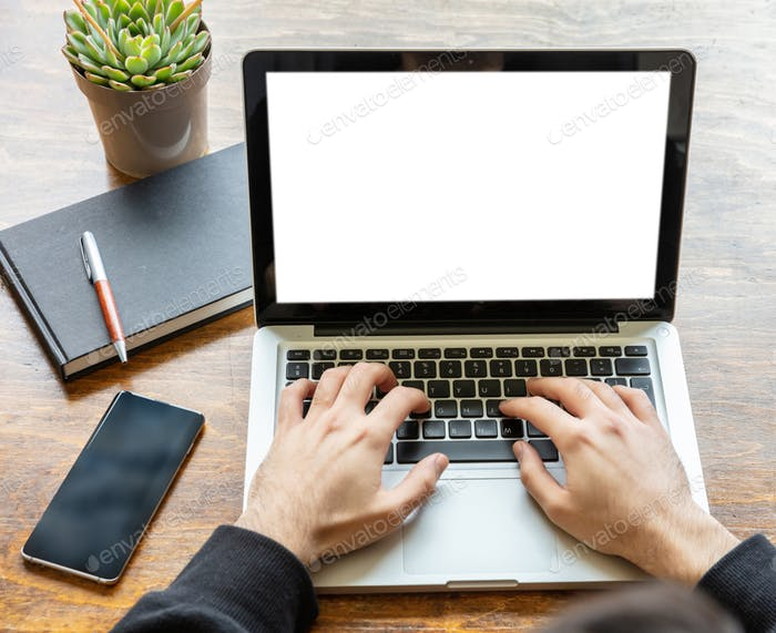 Man working with a laptop with blank screen on a wooden desk, home office concept, copy space
