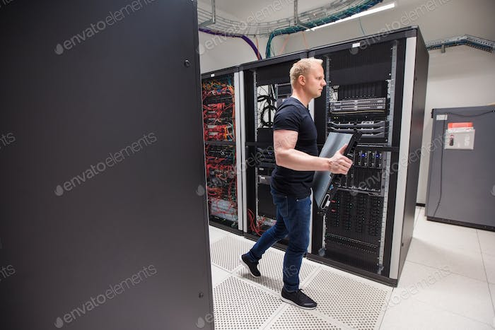 Male Technician Carrying Blade Server While Walking In Datacente
