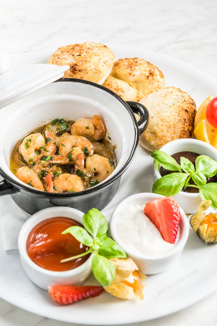 Prawns served on platter with sauces and fresh bread