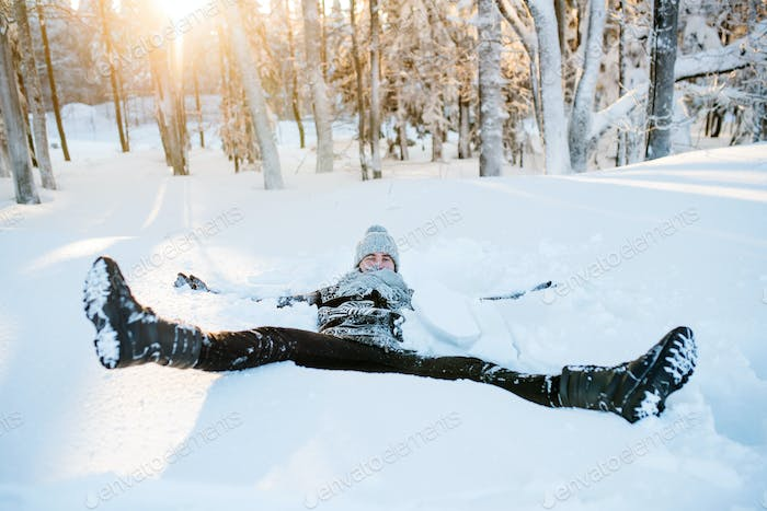 Young man having fun in snow outdoors in winter, lying in snow.