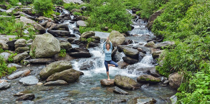 Woman dpoing yoga asana tree pose at waterfall