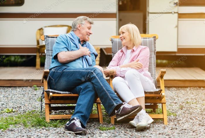 Mature married couple relaxing in lounge chairs in front of camper van outdoors
