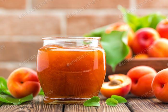 Aprikosenmarmelade in einem Glas und frische Früchte mit Blättern