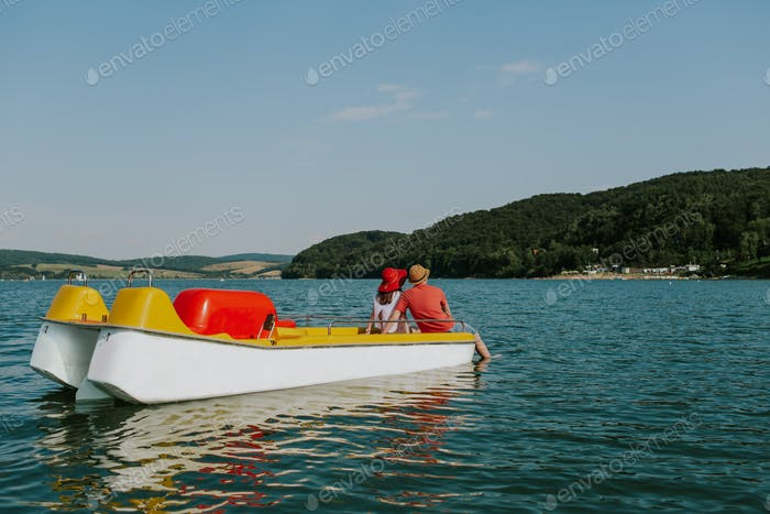 Rear view of couple sitting on pedal boat with feet in the water.