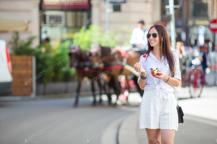 Tourist girl enjoying a stroll through Vienna and looking at the beautiful horses in the carriage