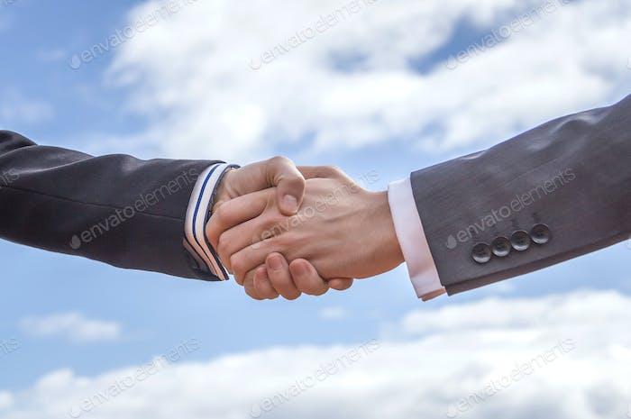 Closeup of business handshake over sky background
