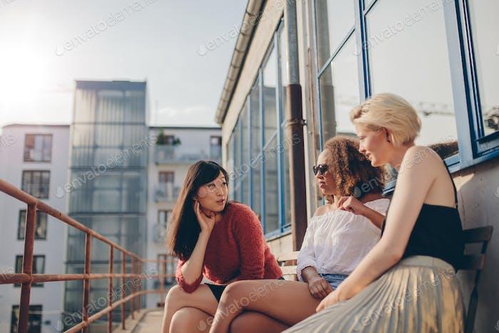 Drei junge Frauen sitzen im Freien und plaudern