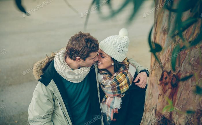Young couple in love embracing and kissing outdoors