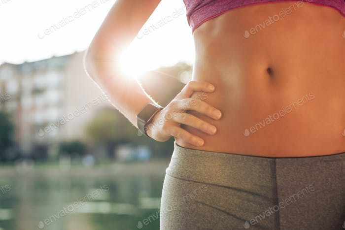 Fit woman's torso with her hands on hips